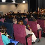 sala kina czyn ludzie siedzą w fotelach w tle scena na scenie orkiestra dęta