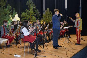 zdjęcie Młodzieżowej Orkiestry Dętej z Poniatowej na scenie obok dyrygent oraz solista w tle choinki