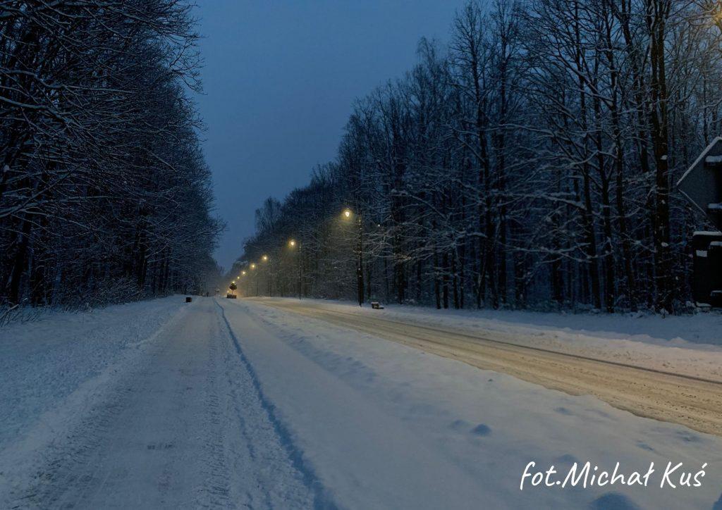zima ul. Fabryczna w Poniatowej zapada zmrok wzdłuż ulicy latarnie po bokach las