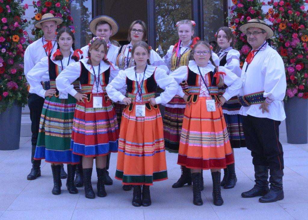członkowie zespołu Dziecięca Kapela Ludowa z poniatowej w strojach ludowych z boku instruktor zespołu w tle kolorowe kwiaty