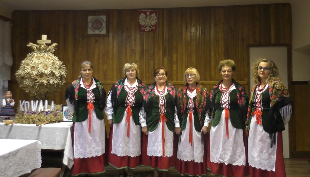 zespół śpiewaczy kowalanki 6 kobiet w strojach ludowych w tle godło obok wieniec dożynkowy