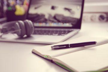 na pierwszym planie notes i długopis w tel otwarty laptop i słuchawki