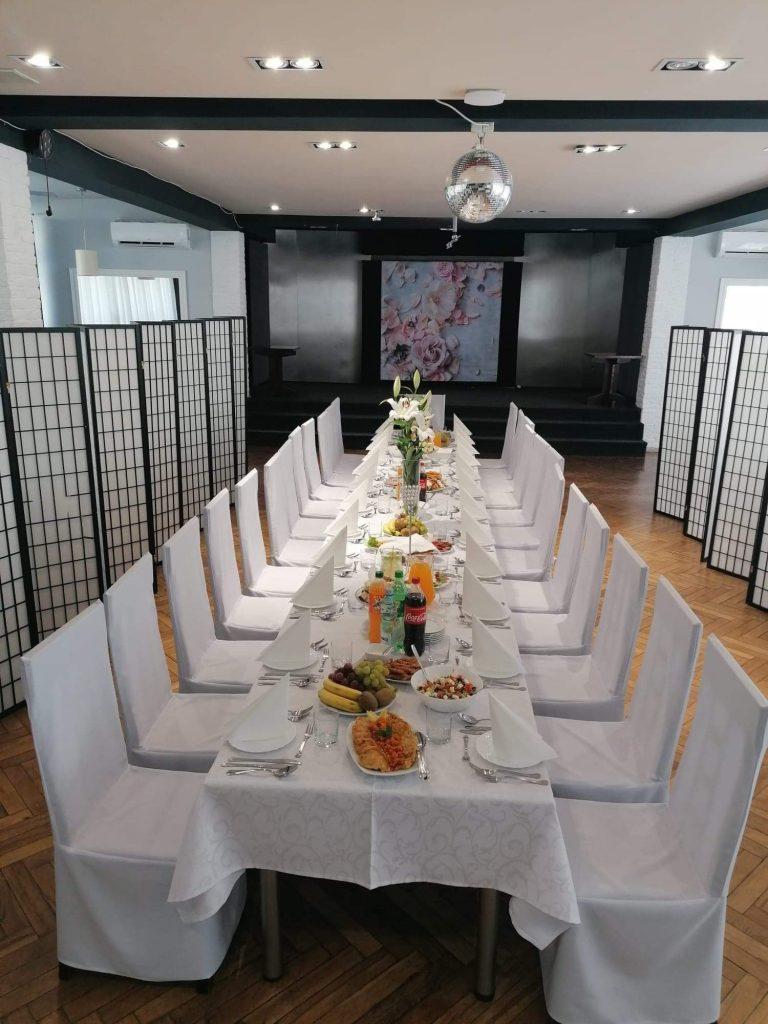 Na zdjęciu wnętrze kawiarni Klubowa, zastawiony potrawami stół, dookoła stoją białe krzesła.