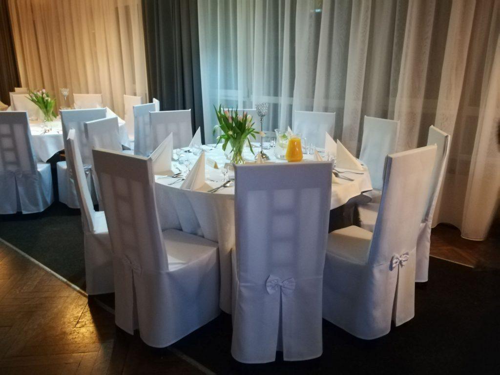 Na zdjęciu wnętrze kawiarni Klubowa, 2 świeżo zastawione okrągłe stoliki, dookoła stoją białe krzesła.