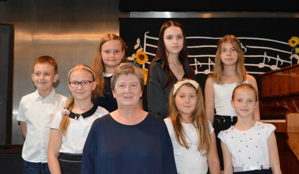 Na zdjęciu stoją uczestnicy zajęć muzycznych z instruktorem pianina Janiną Bednarz. W tle dekoracja z nut.