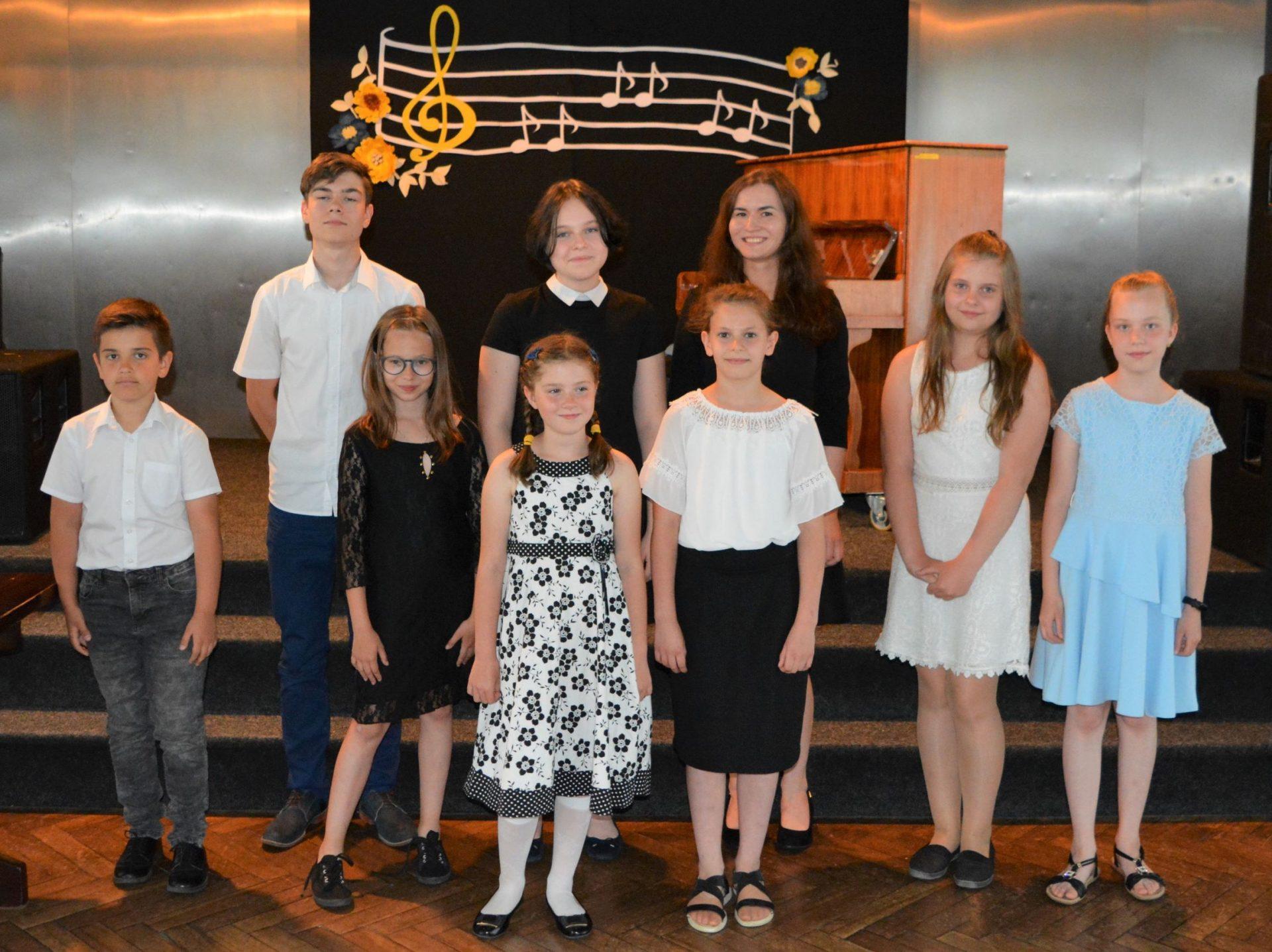 Na zdjęciu stoją uczniowie zajęć muzycznych CKPiT wraz ze swoim instruktorem. Z tyłu na scenie po prawej stoi pianino, w tle dekoracja z nutami.