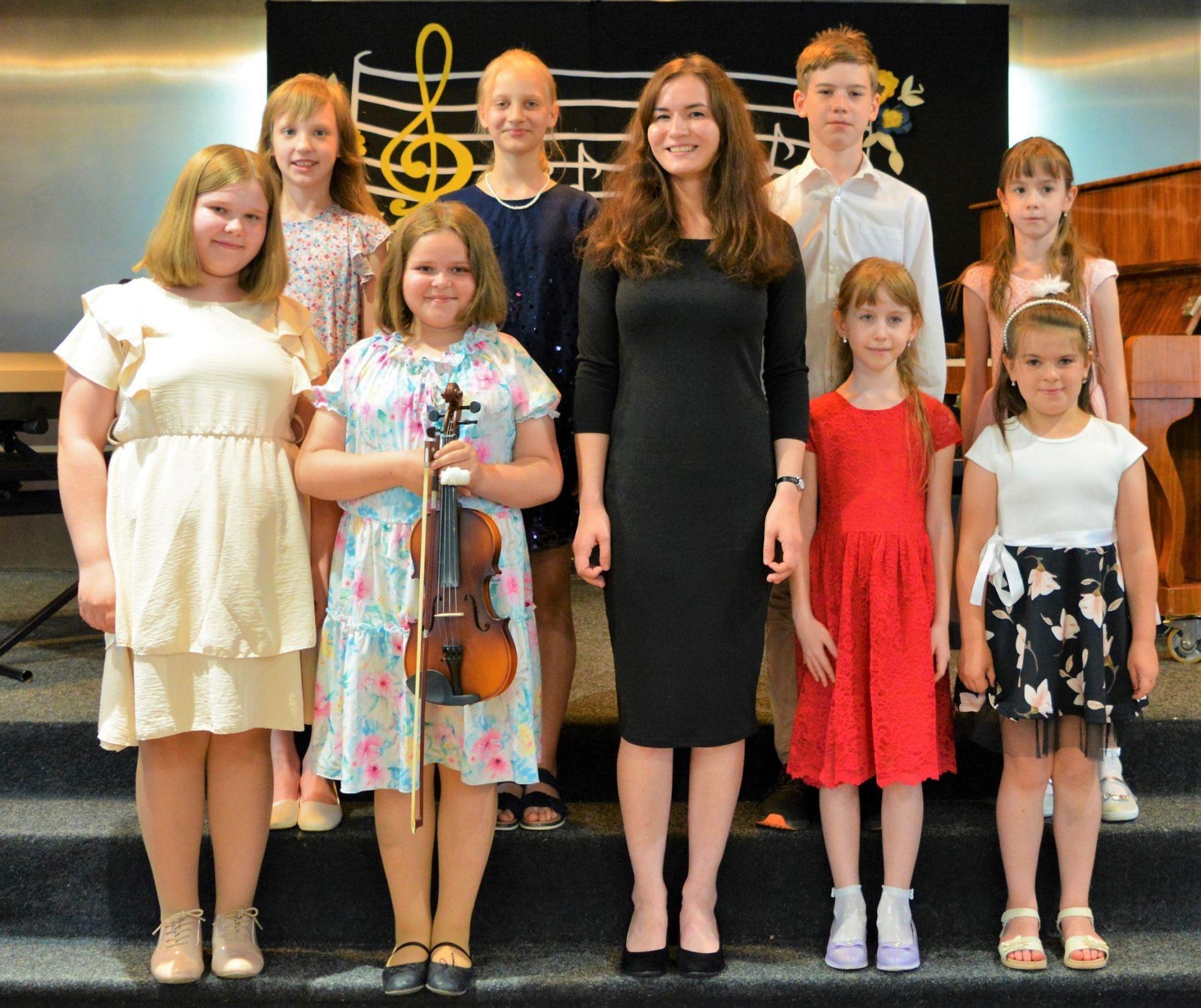 Na zdjęciu stoją uczniowie zajęć muzycznych CKPiT wraz ze swoim instruktorem. Z tyłu na scenie po lewej stoi keyboard, po prawej pianino, w tle dekoracja z nutami.