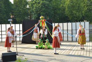 zdjęcie park miejski grupa dzieci ubrana na ludowo stoi na scenie