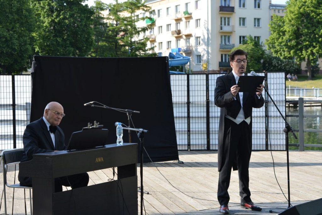 zdjęcie dwaj mężczyźni w garniturach jeden gra na pianinie drugi śpiewa do mikrofonu w tle budynki