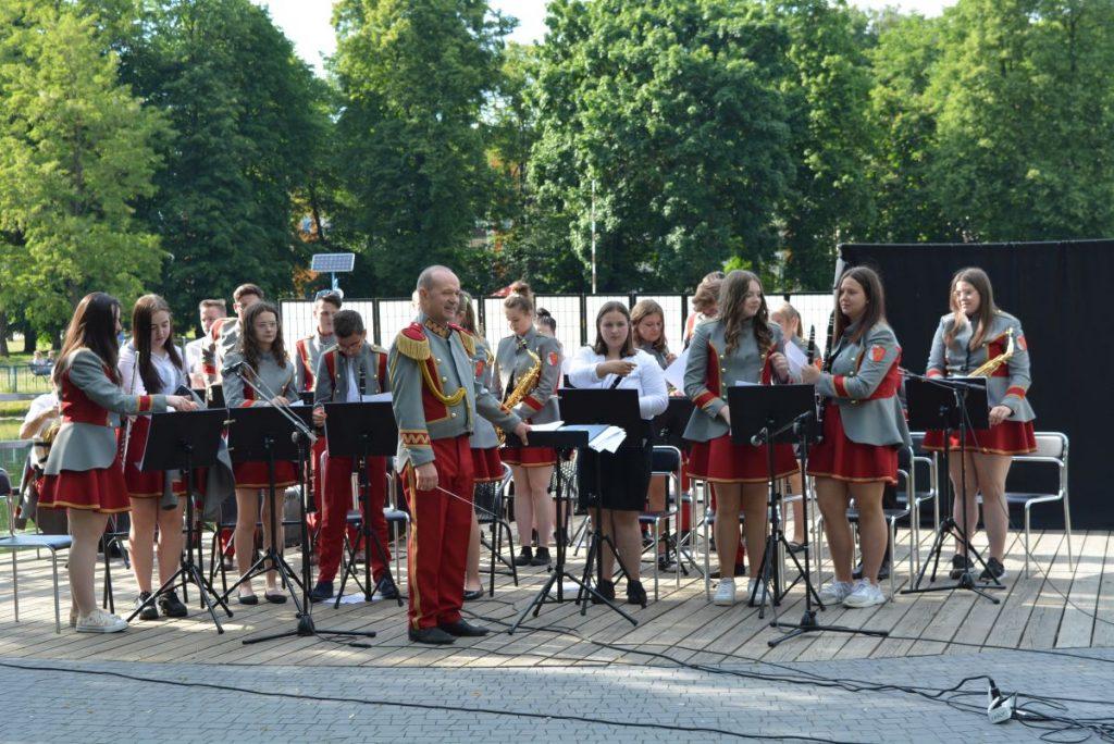 zdjęcie młodzieżowa orkiestra dęta - grupa młodzieży w mundurach orkiestry z kapelmistrzem w tle drzewa