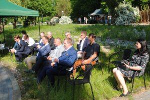 zdjęcie grupa ludzi siedzi na krzesłach w parku