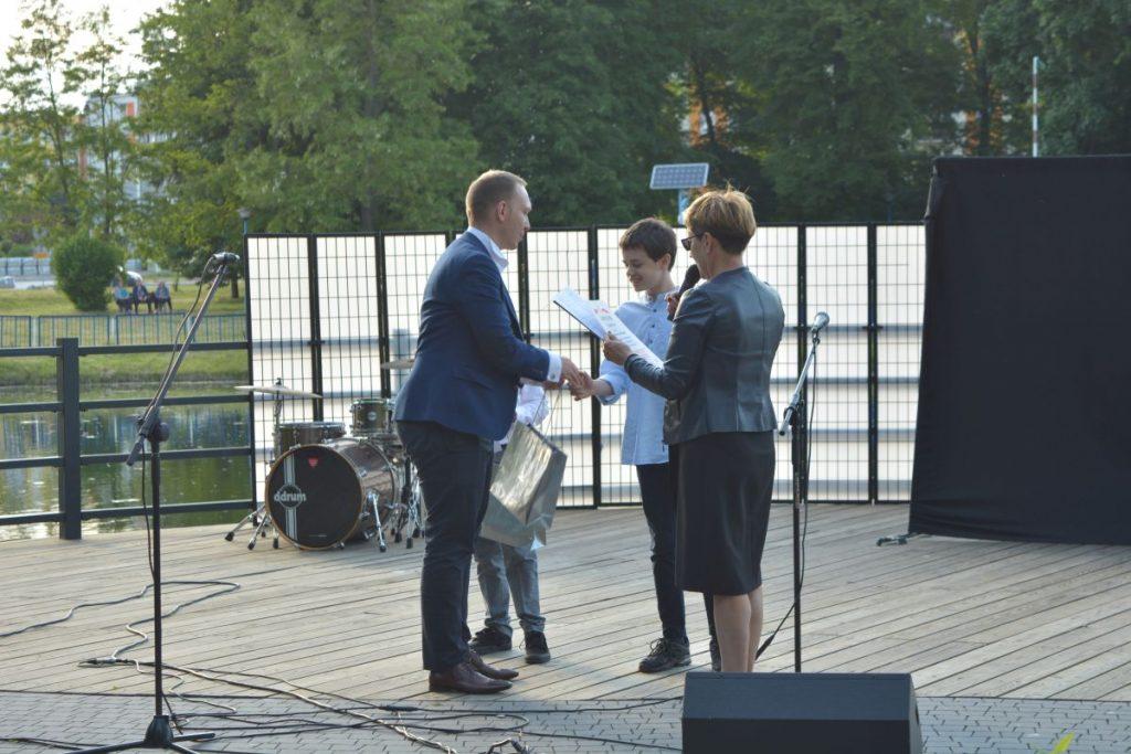 zdjęcie mężczyzna w marynarce wręczający nagrodę na scenie chłopcu obok kobieta z mikrofonem