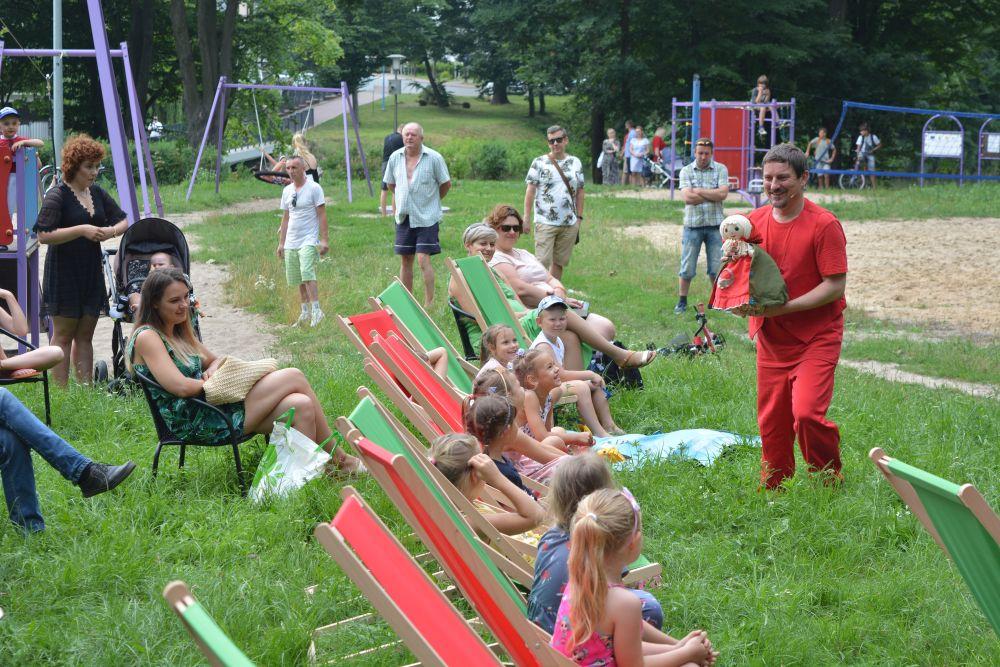 zdjęcie aktor w czerwonym stroju z lalką w ręce stoi obok dzieci siedzących na leżakach na trawie