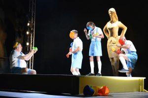 zdjęcie czterech aktorów na scenie ubranych w błękitne krótkie spodnie w tle figura kobiety