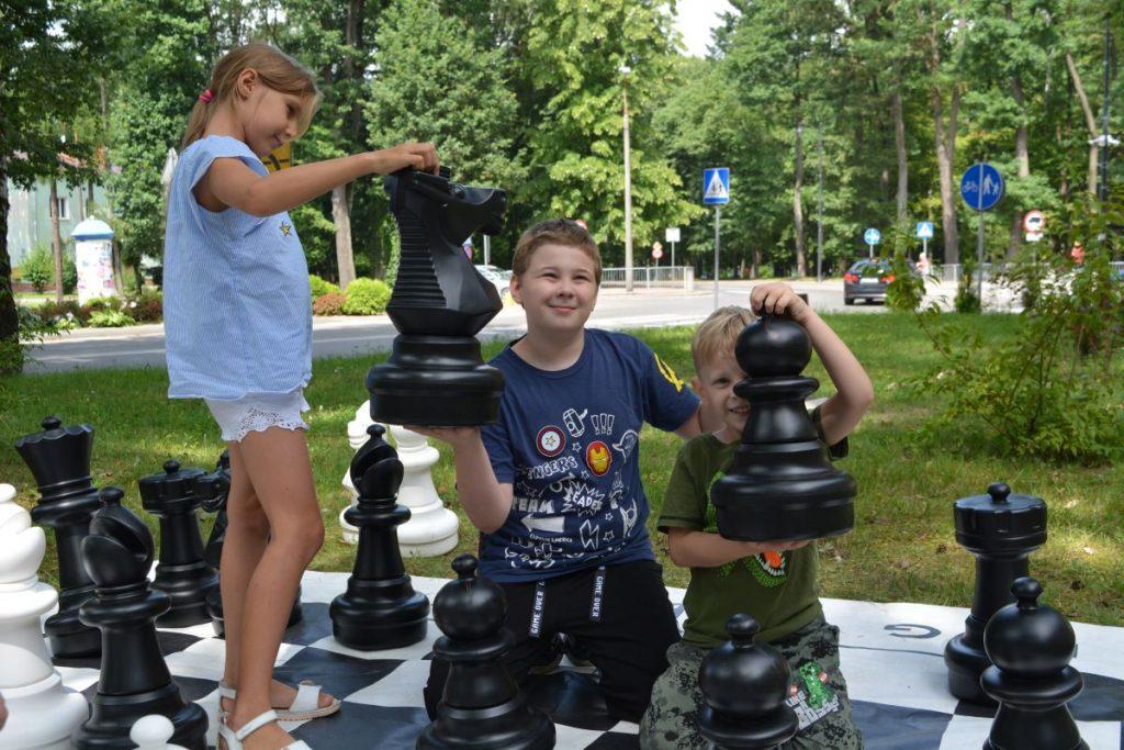 zdjęcie troje dzieci trzyma duże figury szachowe w tle zielone drzewa