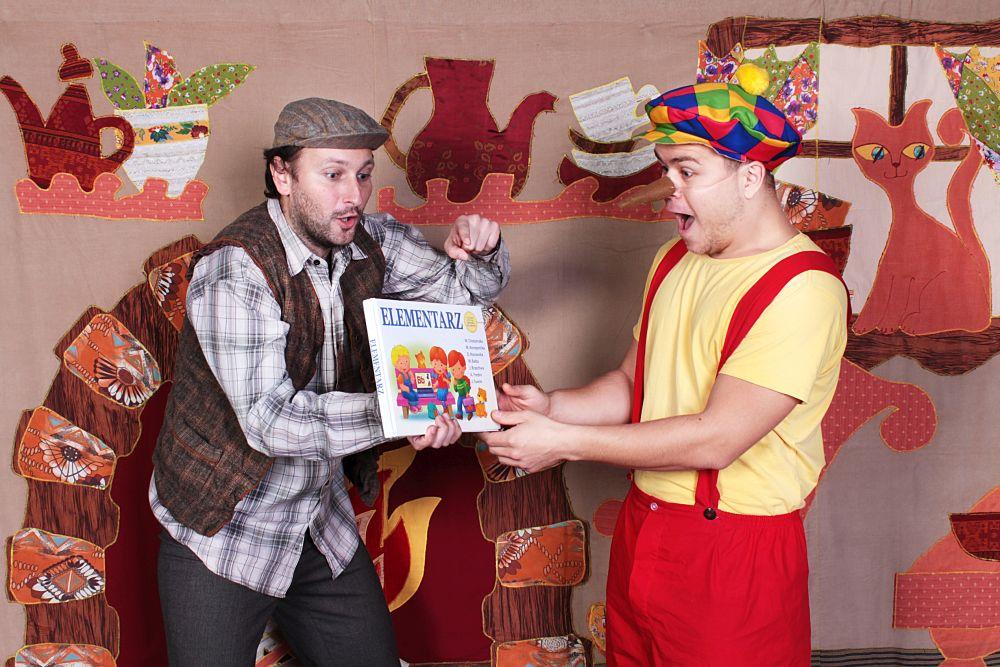 zdjęcie dwóch aktorów teatru jeden trzyma książkę drugi ma długi noc w tle dekoracja ogień w kominku i kot