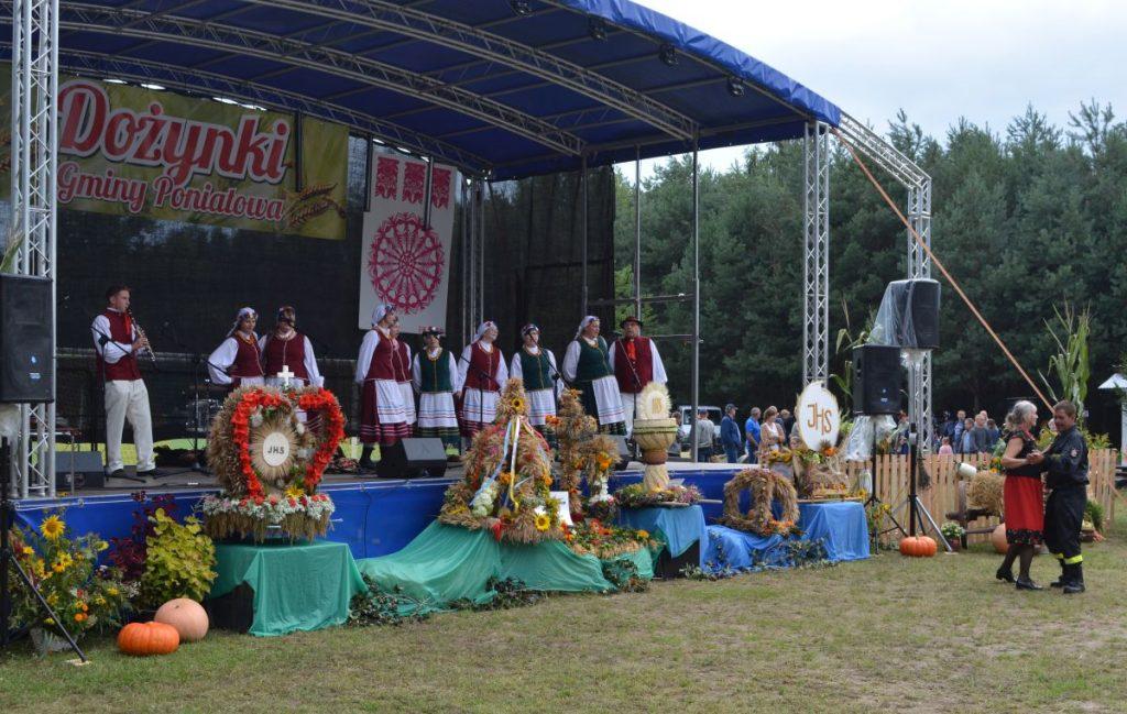 zdjęcie zespól ludowy na scenie na pierwszym palnie wieńce dożynkowe i tańcząca para
