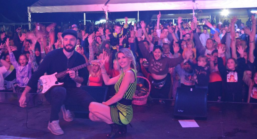 zdjęcie koncert w tle publiczność na pierwszym planie blondynka w sukience i mężczyzna z gitarą