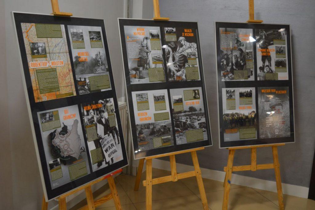 zdjęcie wystawa trzy sztalugi ze zdjęciami w tle szara ściana