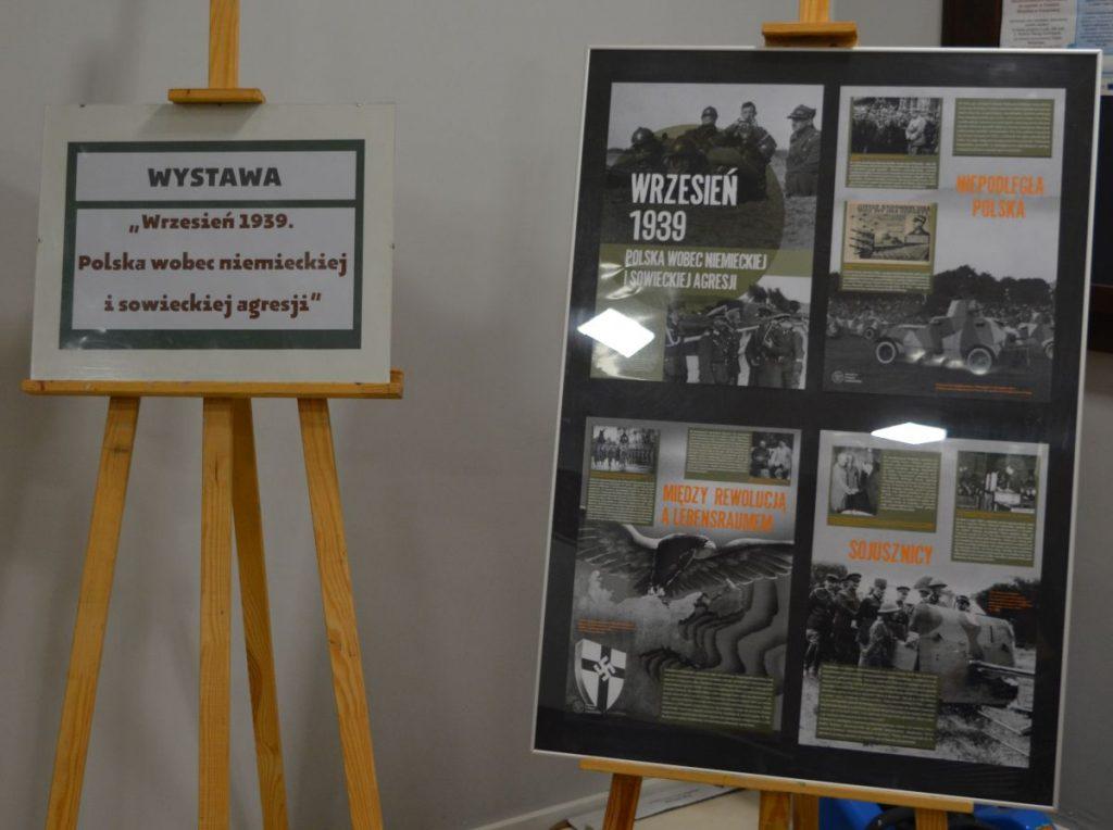 zdjęcie wystawa dwie sztalugi ze zdjęciami w tle szara ściana napis wystawa wrzesień 1939